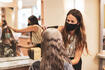 hairdresser with mask enjoying to work again in her hair salon after lockdown is over