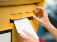 Woman's Hands Inserting Letter In Mailbox