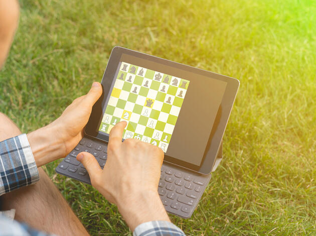 playing chess on a digital device outdoor, mental activity