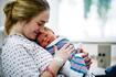 New mom holds her baby in hospital bed
