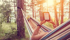 Young girl in a hammock with e-book