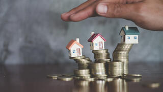 Hand protection, house model on top of stack of money as growth of mortgage credit, Concept of property management. Invesment and Risk Management, Copy space