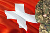 Crossed arms Swiss soldier with national waving flag on background - Switzerland Military theme.